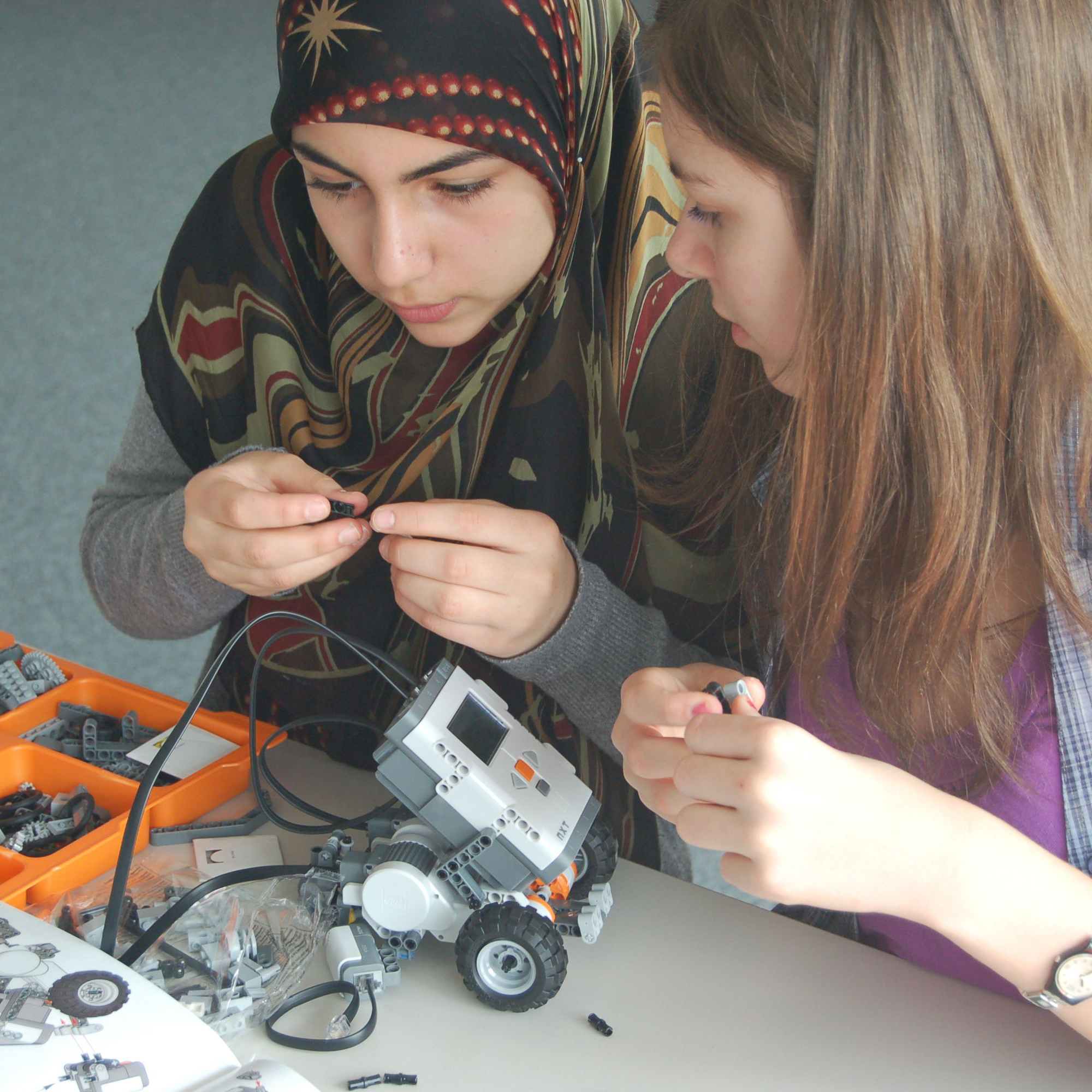 Two female pupils building a robot