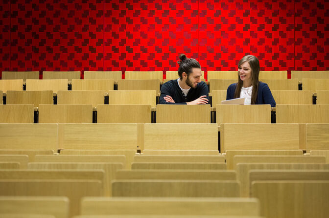 Two students in a lecture hall